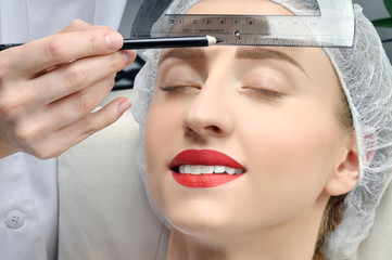 Microblading. Permanent makeup. Attractive woman getting facial care and tattoo