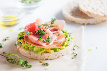 Crisp bread healthy snack with Parma ham, avocado spread, olive oil, thyme. Easy breakfast close-up on a white background with copy space.