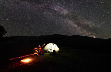 Father and two children tourists resting at night camping in mountains, sitting on log beside campfire and glowing tent, looking at incredible beautiful starry sky and Milky way. Man pointing at sky