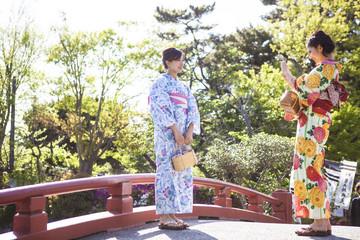和服女性たちが橋の上で写真を撮っている