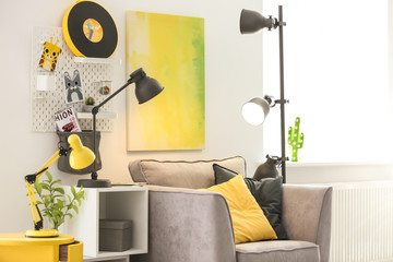 Room interior with modern lamps and comfortable armchair