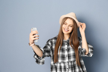 Young beautiful woman taking selfie against grey background