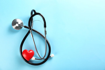 Stethoscope and small red heart on color background. Heart attack concept