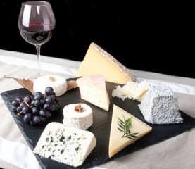 Assorted Cheese Plate with Red Wine, vine and Honey on black background
