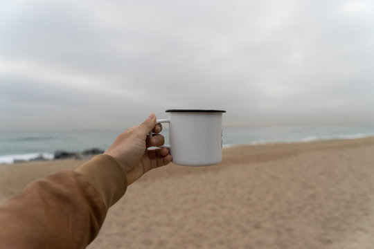 Mockup of metal camping aluminum cup or mug, girl in leather jacket holds out on cloudy day at beach, concept adventures and nomad lifestyle