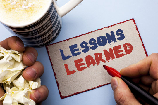 Writing note showing  Lessons Learned. Business photo showcasing Experiences that should be taken into account in the future written by Man on Cardboard Piece Holding Marker on the plain background