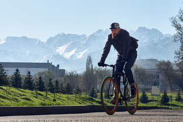 A man with the black bicycle goes against the background of big mountains in the city of Almaty