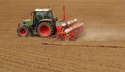 Tractor with a modern sowing seeds machine in a newly plowed field in springtime. Side back view, with only plowed land as a background