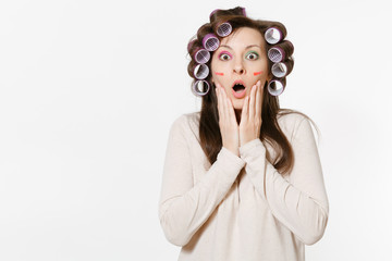 Shocked woman with curlers on hair standing isolated on white background. Crazy makeup with set facial decorative cosmetics. Beauty female fashion lifestyle concept. Advertisement area to copy space.