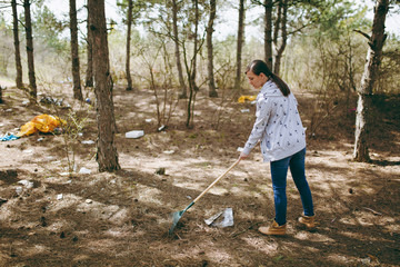 Young woman in casual clothes cleaning rubbish using rake for garbage collection in littered park or forest. Problem of environmental pollution. Stop nature garbage, environment protection concept.