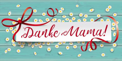 Danke Mama Banner mit Papierzettel auf einem Holztisch mit Gänseblümchen