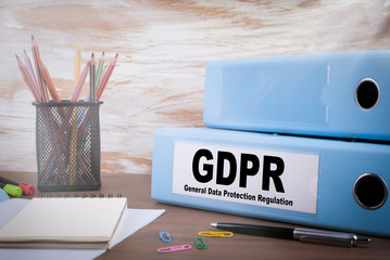 GDPR General Data Protection Regulation concept. Office Binder on Wooden Desk. On the table colored pencils, pen, notebook paper
