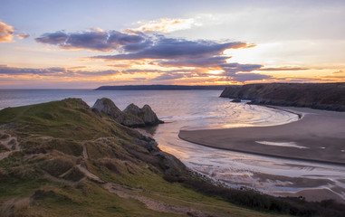 landscape image of three cliffs bay at sunset with the tide in  Wall mural
