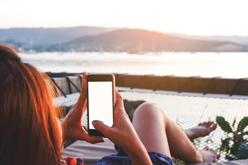 Young woman using black smartphone with blank desktop screen while lying side the sea with evening sunset background.