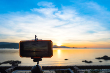 Smartphone camera stand on tripod photographing scenic of evening sunset over tropical sea and mountain.