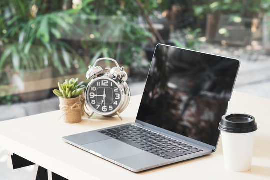 Blank black laptop screen display on wooden table with a cup of coffee, clock and small plant pots in office while break time.