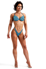 Sexy woman bodybuilder is posing against white background, isolated