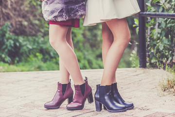 Two women presenting shoes outdoor