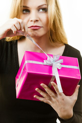 Curious woman holding gift box