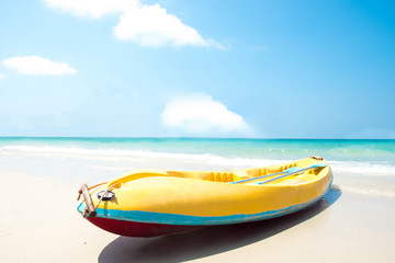 Kayak yellow parked waiting for tourists on the beach with a blue sky and a beautiful sea.