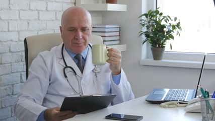 Confident Doctor Enjoy a Cup of Tea and Read Documents