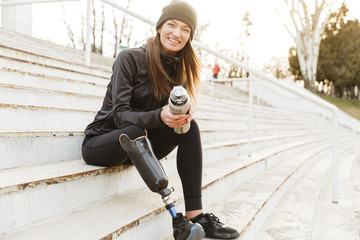 Strong willed handicapped woman in black tracksuit with prosthetic leg laughing, while sitting at the street stairs with thermos cup in hands
