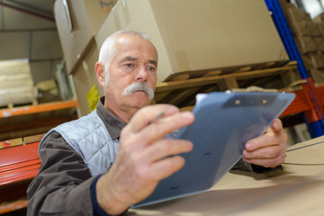 senior worker holding clipboard in warehouse