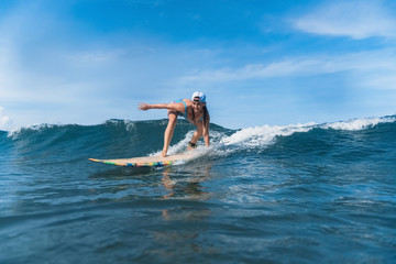 woman in swimming suit and cap surfing in ocean