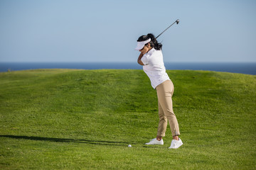 Sportive woman playing golf on green meadow