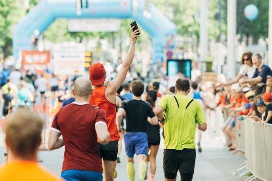 Mann macht freudig ein Foto beim Laufen mit Smartphone beim Marathon