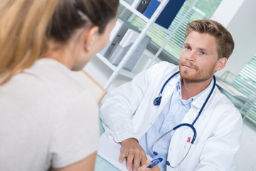handsome doctor during consultation with female patient