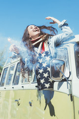 Brunette woman with bengal and American scarf in the old van