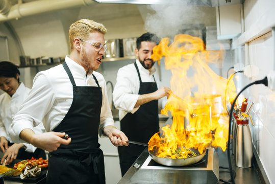 Chefs cooking flambe in the kitchen