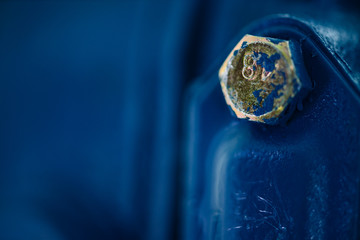Blue metal rough surface of part with gold bolt. Blue painted of auto part. Automotive grunge background image.