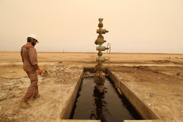 A worker walks past the oil well at the Sindbad oil field near the Iraqi-Iranian border in Basra