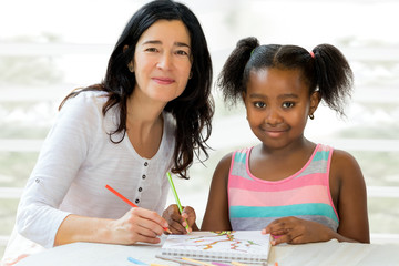 Little african girl and  teacher drawing together.