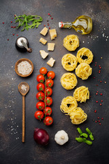 ngredients for traditional Italian pasta dish. Uncooked raw spaghetti, parmesan cheese, olive oil, pepper, cherry tomatoes on old dark stone background.