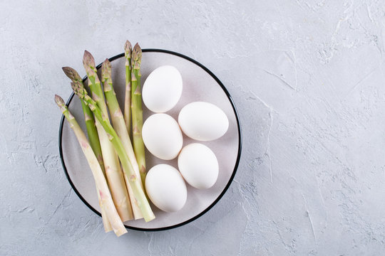 Preparation of asparagus and eggs. Simple products for a healthy breakfast. Space for text Background for a recipe.