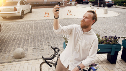 Portrait of stylish hipster man making selfie on vintage bicycle