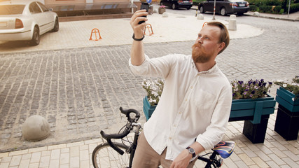 Handsome bearded man making selfie on vintage bicycle on street