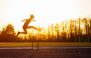 Athletic woman jumping above the hurdle on stadium running track during sunset