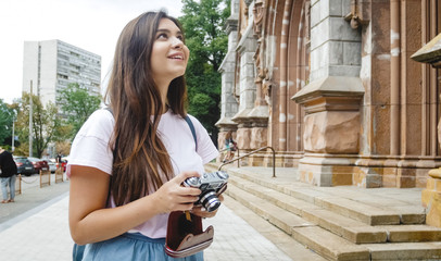 Beautiful smiling brunette tourist girl looking at old cathedral