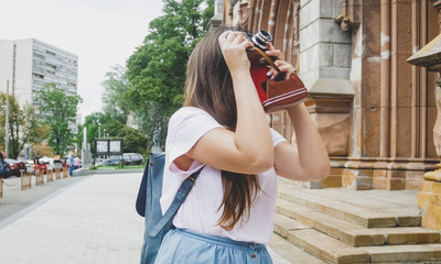 Beautiful brunette tourist girl making image of old cathedral on vintage film camera