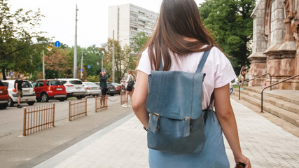 Rear view image of young girl with bag and vintage film camera walking on street