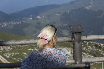 Blonde woman is sitting on themountains background