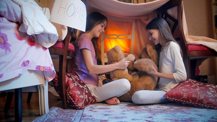 Two cheerful girls playing with teddy bears in bedroom at night