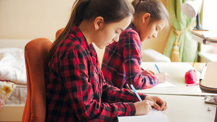 Toned portrait of two girls doing homework behind desk at big window