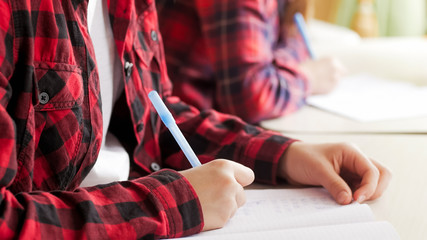 Closeup shot of two sisters writing homework with pens