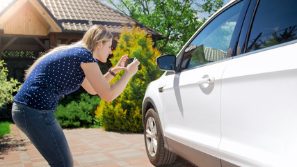Young woman taking photographs of her car on mobile phone