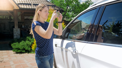 Portrait of young female driver making photographs of her car